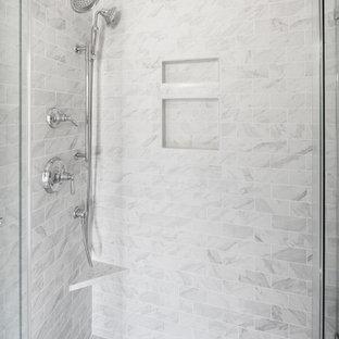 Foto de cuarto de baño con ducha, tradicional renovado, de tamaño medio, con armarios estilo shaker, puertas de armario blancas, ducha esquinera, sanitario de dos piezas, baldosas y/o azulejos grises, baldosas y/o azulejos blancos, baldosas y/o azulejos de mármol, paredes grises, suelo vinílico, lavabo bajoencimera, encimera de cuarcita, suelo gris y ducha con puerta con bisagras