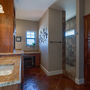 Bathroom - large rustic master gray tile and porcelain tile concrete floor and brown floor bathroom idea in Austin with raised-panel cabinets, medium tone wood cabinets, beige walls, an undermount sink and granite countertops