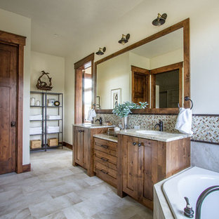 Large mountain style master limestone floor drop-in bathtub photo in Salt Lake City with shaker cabinets, medium tone wood cabinets, beige walls and an undermount sink
