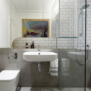 This is an example of a contemporary bathroom in Sydney with a wall-mount toilet, gray tile, white tile, subway tile, multi-coloured walls and a wall-mount sink.