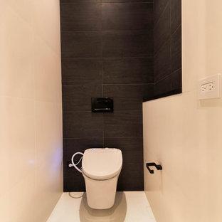 Idee per una stanza da bagno moderna con ante lisce, ante bianche, vasca da incasso, doccia alcova, WC monopezzo, piastrelle bianche, piastrelle in gres porcellanato, pareti grigie, pavimento in gres porcellanato, lavabo sottopiano, top in acciaio inossidabile, pavimento bianco, doccia aperta e top nero