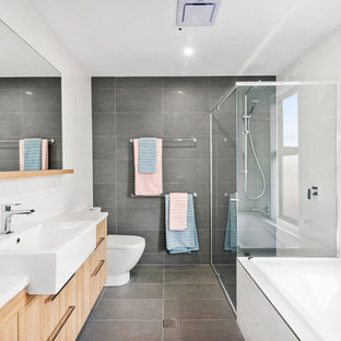 Design ideas for a contemporary bathroom in Gold Coast - Tweed with flat-panel cabinets, medium wood cabinets, a drop-in tub, a corner shower, gray tile, white walls, a drop-in sink, grey floor, a sliding shower screen and white benchtops.