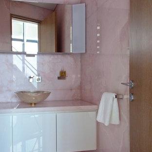 Idéer för små funkis rosa badrum för barn, med släta luckor, vita skåp, ett fristående badkar, en kantlös dusch, en toalettstol med hel cisternkåpa, rosa kakel, stenhäll, rosa väggar, ett fristående handfat, bänkskiva i onyx, rosa golv och dusch med skjutdörr