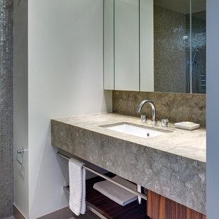 Kleines Modernes Badezimmer mit flächenbündigen Schrankfronten, hellbraunen Holzschränken, grauen Fliesen, Unterbauwaschbecken, Kalkstein-Waschbecken/Waschtisch, Duschnische, Toilette mit Aufsatzspülkasten, Porzellan-Bodenfliesen und Kalkfliesen in New York