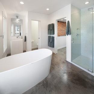 Inredning av ett industriellt stort en-suite badrum, med ett piedestal handfat, ett fristående badkar, en dusch i en alkov, vit kakel, mosaik och betonggolv