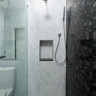 Alcove shower - mid-sized contemporary 3/4 black tile, gray tile, white tile and stone tile marble floor alcove shower idea in DC Metro with flat-panel cabinets, gray cabinets, solid surface countertops, a one-piece toilet, an undermount sink and gray walls