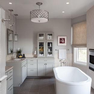 Diseño de cuarto de baño principal, clásico renovado, grande, con lavabo bajoencimera, armarios estilo shaker, puertas de armario grises, bañera exenta, baldosas y/o azulejos blancos, paredes grises, ducha empotrada, baldosas y/o azulejos de mármol, suelo de pizarra, encimera de esteatita, suelo gris y ducha con puerta con bisagras