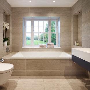 Klassisk inredning av ett stort en-suite badrum, med släta luckor, skåp i mörkt trä, ett badkar i en alkov, en vägghängd toalettstol, grå kakel, porslinskakel, grå väggar, klinkergolv i porslin och ett väggmonterat handfat