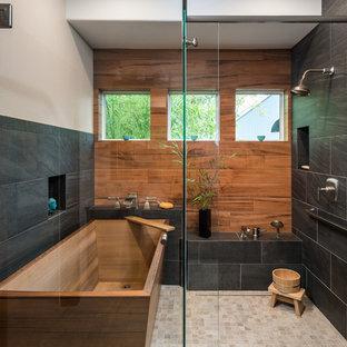 Bild på ett vintage badrum, med ett fristående badkar, en dusch i en alkov, svart kakel, brun kakel, porslinskakel, beige väggar, klinkergolv i porslin, beiget golv och dusch med gångjärnsdörr