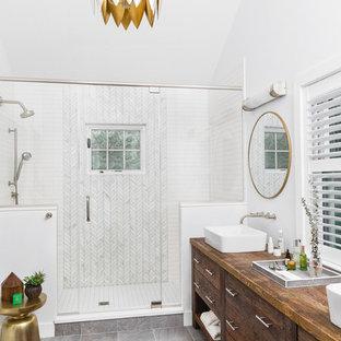 Пример оригинального дизайна: главная ванная комната среднего размера в классическом стиле с плоскими фасадами, темными деревянными фасадами, открытым душем, белой плиткой, плиткой кабанчик, белыми стенами, полом из керамогранита, настольной раковиной, столешницей из дерева, серым полом, душем с распашными дверями и коричневой столешницей