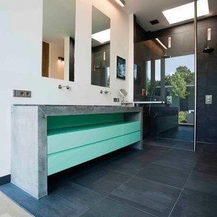 Foto di una grande stanza da bagno padronale contemporanea con ante lisce, ante verdi, vasca freestanding, doccia alcova, WC sospeso, piastrelle grigie, pareti bianche, pavimento con piastrelle in ceramica, lavabo rettangolare e top in cemento