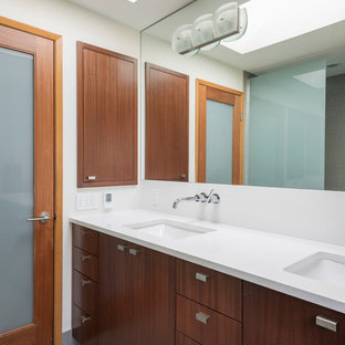 Trendy bathroom photo in Seattle with an undermount sink, flat-panel cabinets, dark wood cabinets and white countertops