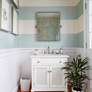 Coastal medium tone wood floor bathroom photo in New York with an undermount sink, marble countertops, white cabinets, multicolored walls and recessed-panel cabinets