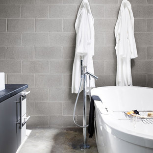 Freestanding bathtub - modern concrete floor freestanding bathtub idea in Austin with gray cabinets