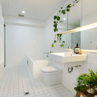 Photo of a mid-sized contemporary 3/4 bathroom in Adelaide with a corner tub, a one-piece toilet, white tile, ceramic tile, white walls, ceramic floors and a wall-mount sink.