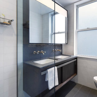 Example of a small minimalist master gray tile and stone slab limestone floor doorless shower design in New York with an undermount sink, flat-panel cabinets, dark wood cabinets, granite countertops, a wall-mount toilet and white walls