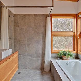 Ejemplo de cuarto de baño principal, moderno, pequeño, con lavabo sobreencimera, armarios con paneles lisos, puertas de armario de madera clara, paredes blancas, suelo de baldosas de cerámica, bañera encastrada, ducha abierta, baldosas y/o azulejos grises, baldosas y/o azulejos de cerámica, encimera de azulejos, suelo gris, ducha con cortina y encimeras grises