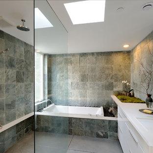 Создайте стильный интерьер: главная ванная комната среднего размера в современном стиле с ванной в нише, серой плиткой, серыми стенами, душем без бортиков, плоскими фасадами, белыми фасадами, унитазом-моноблоком, бетонным полом, столешницей из искусственного камня, врезной раковиной и плиткой из сланца - последний тренд