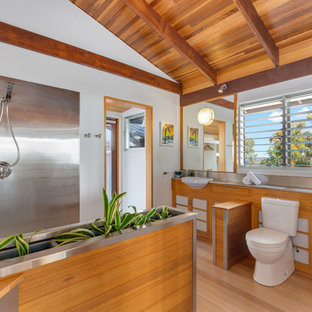 Inspiration for a modern 3/4 bathroom in Other with shaker cabinets, medium wood cabinets, a corner shower, a two-piece toilet, metal tile, white walls, light hardwood floors, a drop-in sink, stainless steel benchtops and an open shower.