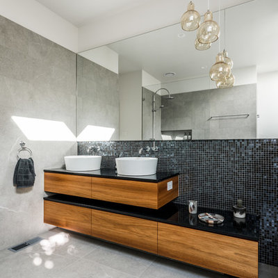 Trendy master black tile and mosaic tile ceramic tile bathroom photo in Melbourne with a vessel sink, flat-panel cabinets, medium tone wood cabinets and white walls