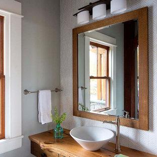 Foto de cuarto de baño rural, pequeño, con armarios tipo mueble, puertas de armario de madera oscura, sanitario de una pieza, baldosas y/o azulejos verdes, baldosas y/o azulejos de vidrio, paredes verdes, suelo de mármol, lavabo sobreencimera, encimera de madera, suelo gris y encimeras marrones