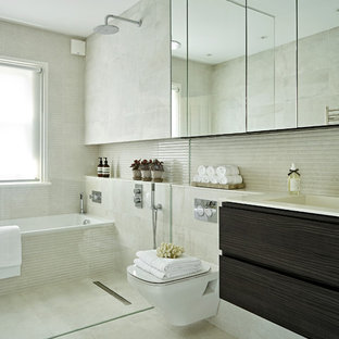 This is an example of a medium sized contemporary wet room in London with flat-panel cabinets, dark wood cabinets, a wall mounted toilet, grey tiles, porcelain tiles, porcelain flooring, grey floors, an open shower, white worktops, an alcove bath and an integrated sink.