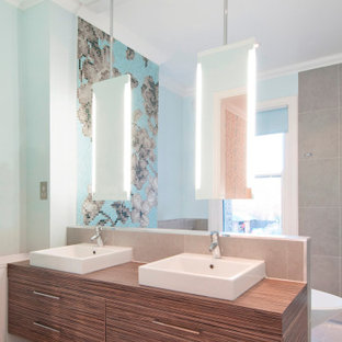 Photo of a large contemporary bathroom in London with flat-panel cabinets, medium wood cabinets, wooden worktops, grey floors, brown worktops, double sinks, a floating vanity unit, a freestanding bath, a wall mounted toilet, grey tiles, mosaic tiles, blue walls, porcelain flooring, a console sink and an open shower.