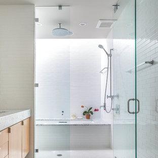 Modelo de cuarto de baño contemporáneo con armarios con paneles lisos, puertas de armario de madera oscura, combinación de ducha y bañera, baldosas y/o azulejos blancos y paredes blancas