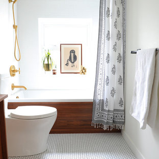 This is an example of a small midcentury ensuite bathroom in Vancouver with flat-panel cabinets, medium wood cabinets, an alcove bath, a shower/bath combination, a two-piece toilet, white tiles, ceramic tiles, white walls, porcelain flooring, wooden worktops, white floors and a shower curtain.