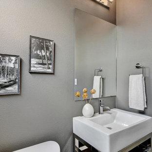 Foto på ett litet funkis badrum med dusch, med öppna hyllor, en toalettstol med hel cisternkåpa, bruna väggar, bambugolv, ett konsol handfat och bänkskiva i akrylsten