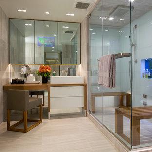 Immagine di una stanza da bagno padronale design di medie dimensioni con consolle stile comò, ante bianche, doccia ad angolo, piastrelle bianche, piastrelle di vetro, pareti grigie, pavimento in gres porcellanato, lavabo a bacinella, top in legno, pavimento beige e porta doccia a battente