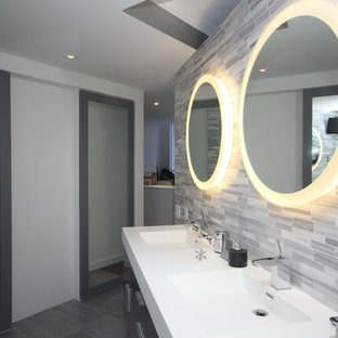 Inspiration for a large contemporary master gray tile and mosaic tile porcelain floor and gray floor bathroom remodel in New York with flat-panel cabinets, black cabinets, white walls, an integrated sink and engineered quartz countertops