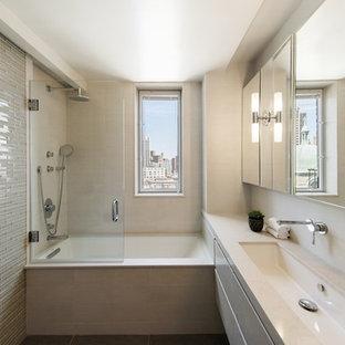 Immagine di una piccola stanza da bagno con doccia contemporanea con ante lisce, ante beige, vasca sottopiano, vasca/doccia, piastrelle grigie, piastrelle di vetro, pareti grigie, lavabo rettangolare, top in superficie solida e doccia aperta