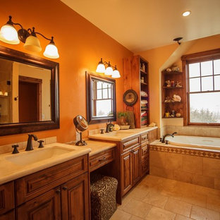 デンバーの中サイズのラスティックスタイルのおしゃれなマスターバスルーム (レイズドパネル扉のキャビネット、中間色木目調キャビネット、ドロップイン型浴槽、オープン型シャワー、一体型トイレ、ベージュのタイル、ベージュの壁、アンダーカウンター洗面器、石タイル、トラバーチンの床、ソープストーンの洗面台、ベージュの床) の写真
