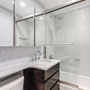 Inspiration for a small modern master gray tile and glass tile marble floor bathroom remodel in New York with an undermount sink, flat-panel cabinets, dark wood cabinets, marble countertops, a two-piece toilet and gray walls