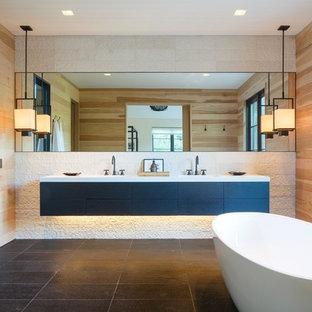 Inspiration för ett mellanstort funkis vit vitt en-suite badrum, med släta luckor, skåp i mörkt trä, ett fristående badkar, våtrum, en toalettstol med hel cisternkåpa, vit kakel, stenkakel, vita väggar, ljust trägolv, ett undermonterad handfat, bänkskiva i akrylsten, svart golv och dusch med gångjärnsdörr