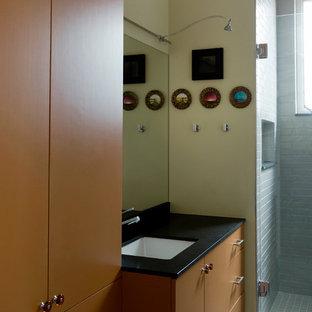 Imagen de cuarto de baño con ducha, tradicional, con armarios con paneles lisos, puertas de armario naranjas, ducha empotrada, baldosas y/o azulejos grises, baldosas y/o azulejos de cerámica, paredes amarillas, suelo de baldosas de porcelana, lavabo bajoencimera y encimera de granito