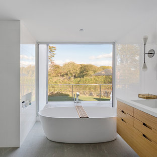 Design ideas for a large modern ensuite bathroom in New York with flat-panel cabinets, medium wood cabinets, a freestanding bath, white tiles, an integrated sink, grey floors, porcelain tiles, engineered stone worktops and white walls.