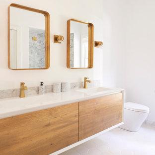 На фото: большая ванная комната в морском стиле с фасадами с утопленной филенкой, фасадами цвета дерева среднего тона, ванной в нише, душем над ванной, унитазом-моноблоком, серой плиткой, мраморной плиткой, белыми стенами, полом из керамической плитки, душевой кабиной, подвесной раковиной, столешницей из ламината, белым полом, душем с распашными дверями и белой столешницей