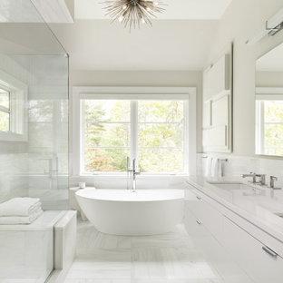 Inredning av ett klassiskt stort vit vitt en-suite badrum, med släta luckor, vita skåp, ett fristående badkar, en hörndusch, vit kakel, porslinskakel, grå väggar, klinkergolv i porslin, ett undermonterad handfat, vitt golv och dusch med gångjärnsdörr
