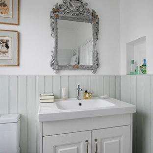 Ispirazione per una stanza da bagno con doccia classica di medie dimensioni con vasca da incasso, vasca/doccia, pavimento in vinile, lavabo integrato, pavimento grigio, ante con bugna sagomata, ante verdi, WC a due pezzi, pareti multicolore e top bianco