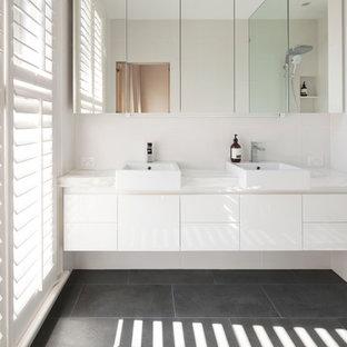 Идея дизайна: маленькая ванная комната в стиле модернизм с настольной раковиной, плоскими фасадами, белыми фасадами, мраморной столешницей, открытым душем, белой плиткой, керамогранитной плиткой, белыми стенами, полом из известняка и душевой кабиной