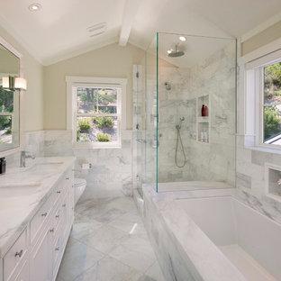 サンタバーバラの広いトラディショナルスタイルのマスターバスルームの画像 (白いタイル、アンダーカウンター洗面器、白いキャビネット、大理石の洗面台、コーナー設置型シャワー、ベージュの壁、大理石の床、アンダーマウント型浴槽、落し込みパネル扉のキャビネット、大理石タイル、白い洗面カウンター、一体型トイレ)