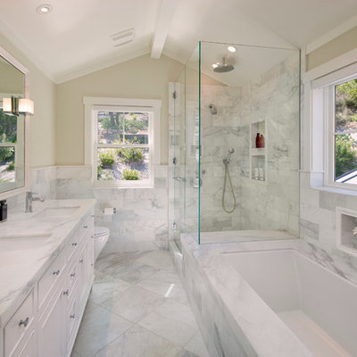 Example of a large classic master white tile and marble tile marble floor corner shower design in Santa Barbara with an undermount sink, white cabinets, marble countertops, beige walls, an undermount tub, recessed-panel cabinets, white countertops and a one-piece toilet