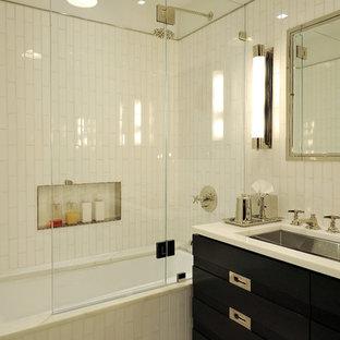 Modernes Badezimmer mit Unterbauwaschbecken, verzierten Schränken, schwarzen Schränken, Unterbauwanne, Duschbadewanne, weißen Fliesen, Metrofliesen und Nische in New York