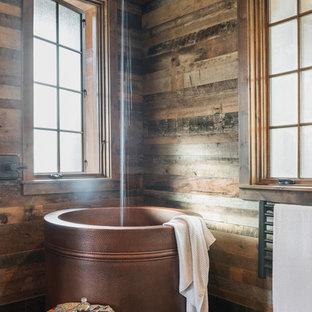 На фото: большая главная ванная комната в стиле рустика с коричневыми стенами, черным полом и японской ванной с