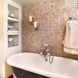 Modelo de cuarto de baño tradicional con bañera con patas, suelo de baldosas tipo guijarro, suelo de cemento y suelo rojo