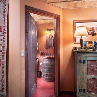 Пример оригинального дизайна интерьера: ванная комната в стиле фьюжн с монолитной раковиной, фасадами островного типа, темными деревянными фасадами, столешницей из меди, оранжевыми стенами, бетонным полом и душевой кабиной