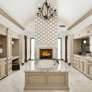 Foto di un'ampia stanza da bagno padronale mediterranea con ante con riquadro incassato, ante beige, vasca sottopiano, pareti bianche, lavabo sottopiano, pavimento in marmo, top in granito e pavimento beige