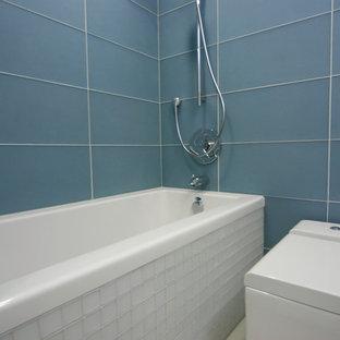 Diseño de cuarto de baño principal, minimalista, pequeño, con bañera empotrada, sanitario de una pieza, baldosas y/o azulejos azules, baldosas y/o azulejos de vidrio, suelo de cemento, armarios abiertos, puertas de armario de madera clara, paredes rosas, lavabo integrado y encimera de cemento